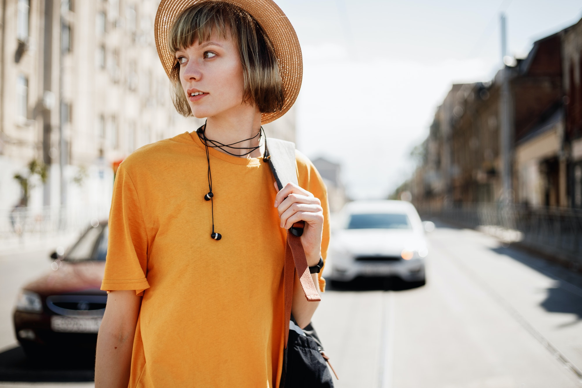 Young girl with headphones in a yellow T-shirt and a straw hat walks with a backpack along a city